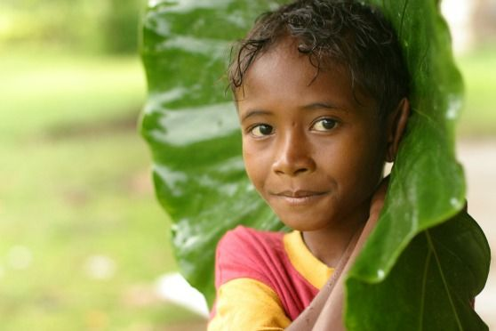 Katuwela, 10, holds a palm frond in the rain in the Trobriand Islands in Milne Bay Province, Papua New Guinea. Photo by Giacommo Pirozzi