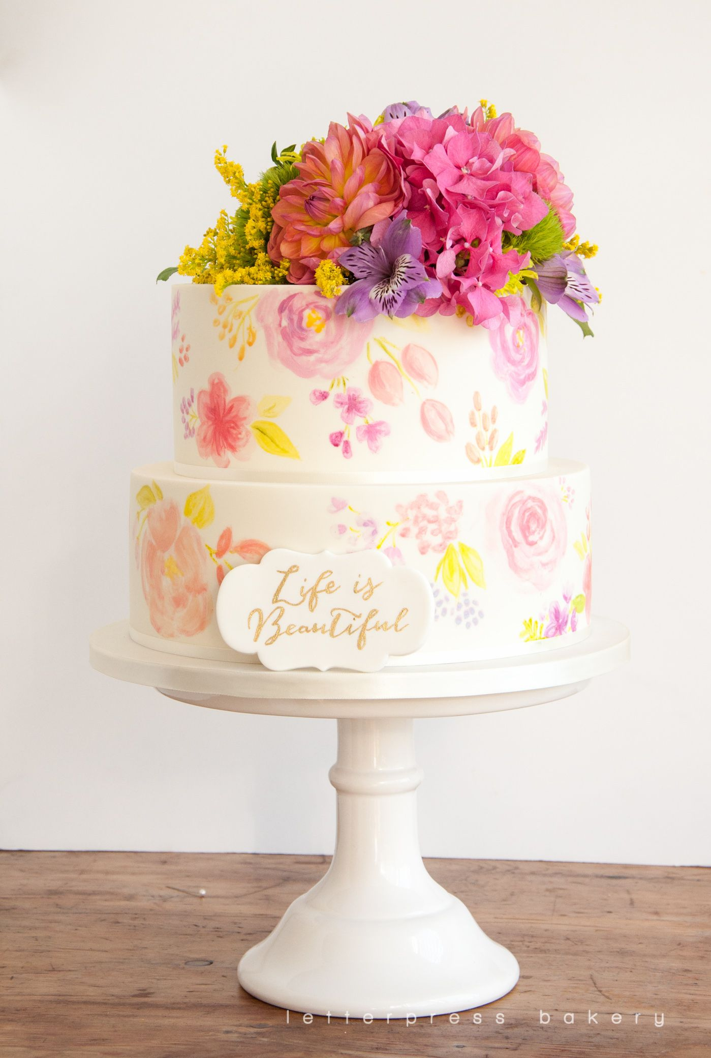 Two tier white birthday cake with water colour painted floral