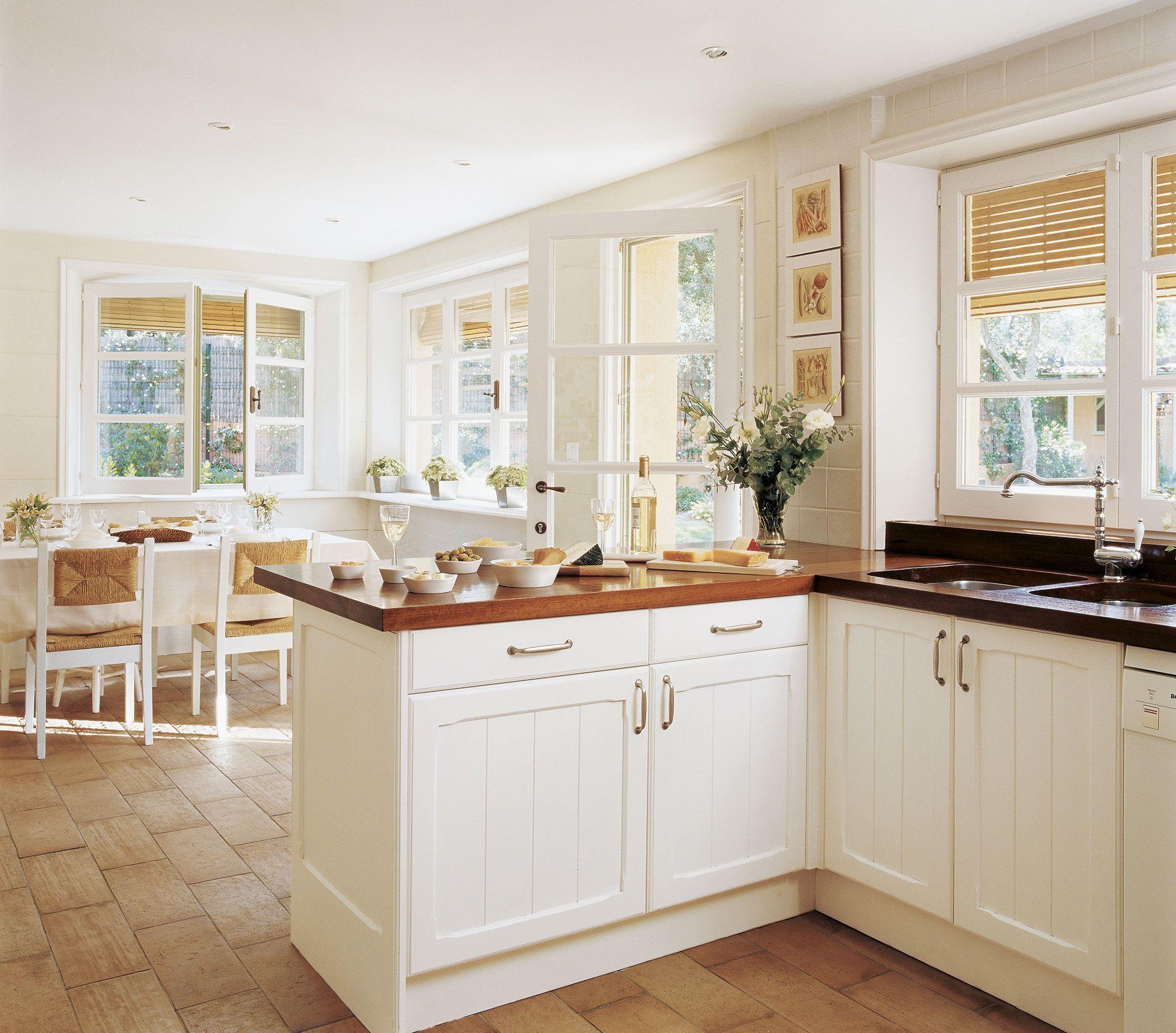 Cocina con península con encimera de madera y office al fondo ...