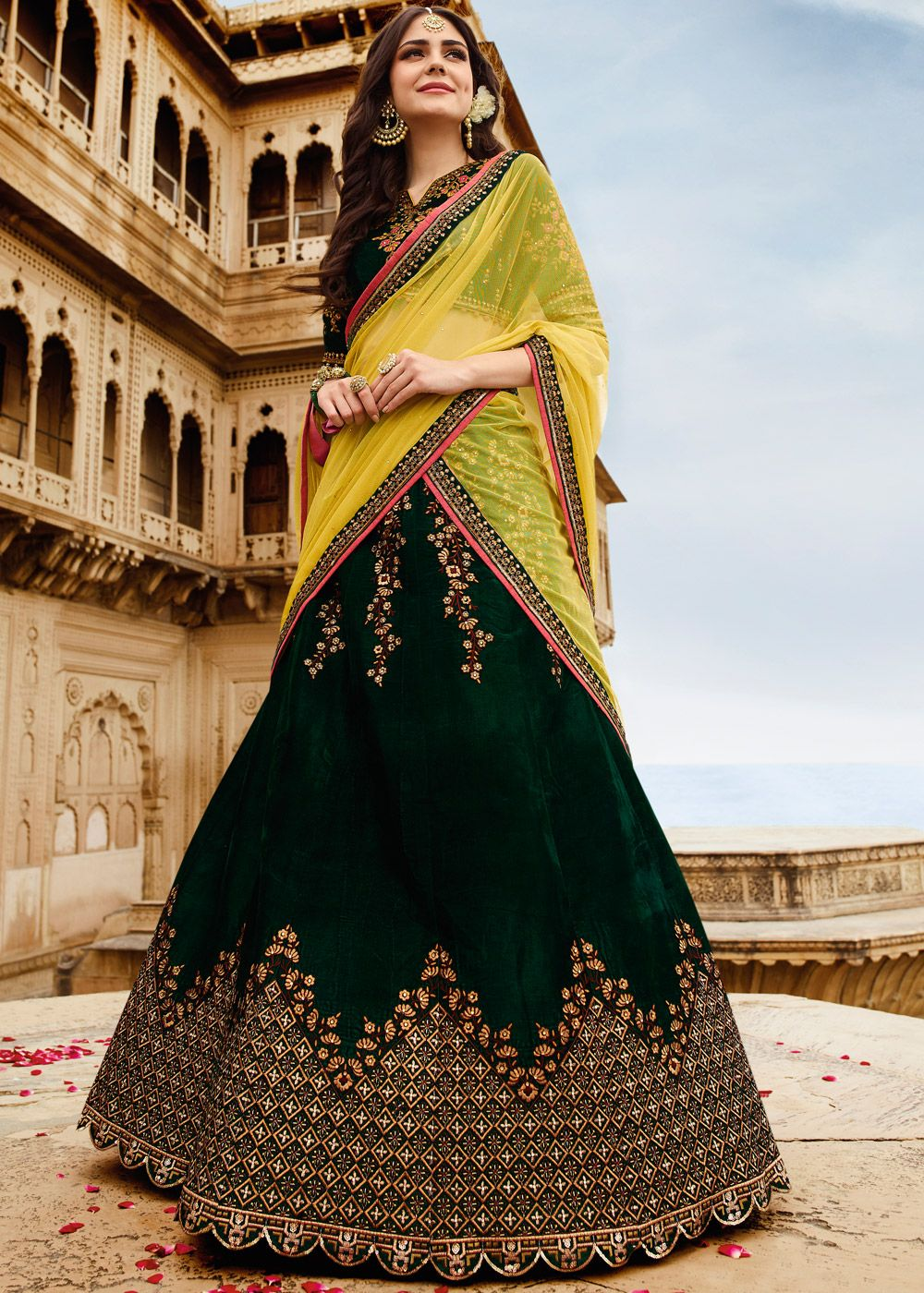60309ea22b Dark green velvet lehenga paired with matching choli enhanced by detailed  floral embroidery. Accompanied by a yellow soft net dupatta in stone work.