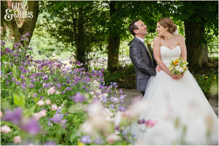 Taitlands Wedding Photography by Tux & Tales Photography  Bride & groom portrait in the flowers. Bride & Groom laughing.