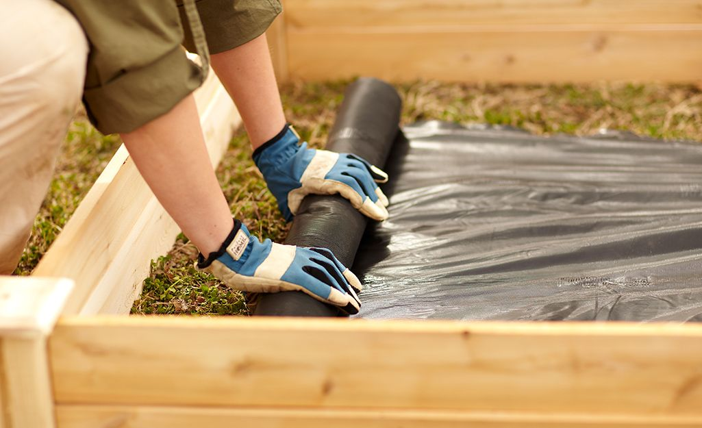 Someone Rolling Out Landscape Liner Instead A Raised Garden Bed Building A Raised Garden Vegetable Garden Raised Beds Raised Garden