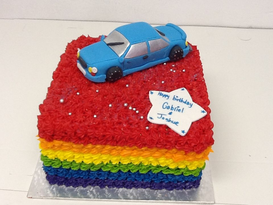 A rainbow birthday cake with a car topper perfect for a young
