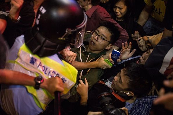 Umbrella Revolution Hong Kong, Pro-democracy protesters lose their balance as police charge towards them in the Mongkok district of Hong Kong on November 26, 2014. Hundreds of Hong Kong police on November 26 cleared a pro-democracy protest camp, arresting Joshua Wong and another student leader and reopening a main road blocked for almost two months. AFP PHOTO / ANTHONY WALLACE (Photo credit should read ANTHONY WALLACE/AFP/Getty Images)