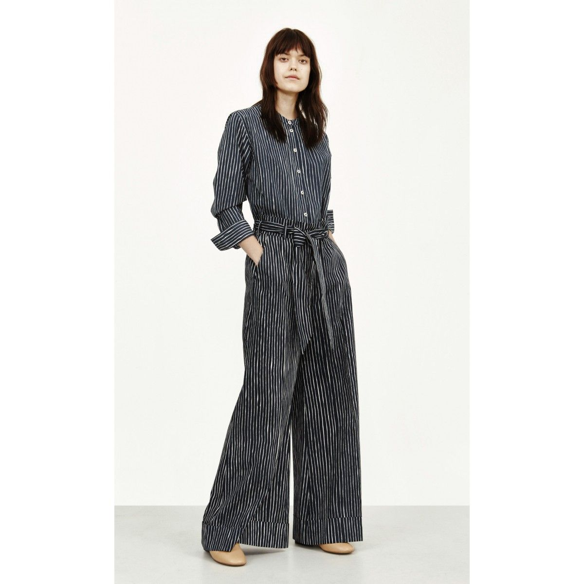 These flat front trousers are made of crisp cotton poplin and feature the Aita print of hand-drawn stripes. They have front diagonal slit pockets and a hidden front clasp and zip front closure. The leg is cut extra wide with a cuff at the hem. Belt loops