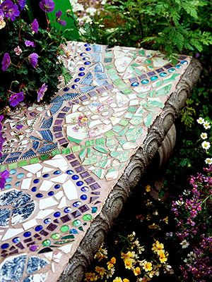 Bench beauty    Ribbons of square glass tiles entwine on the surface of a concrete garden bench. The pattern also includes blue glass pebbles and pieces of an heirloom cake plate.