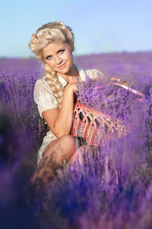 Beautiful blonde woman with lavendar in blossom field