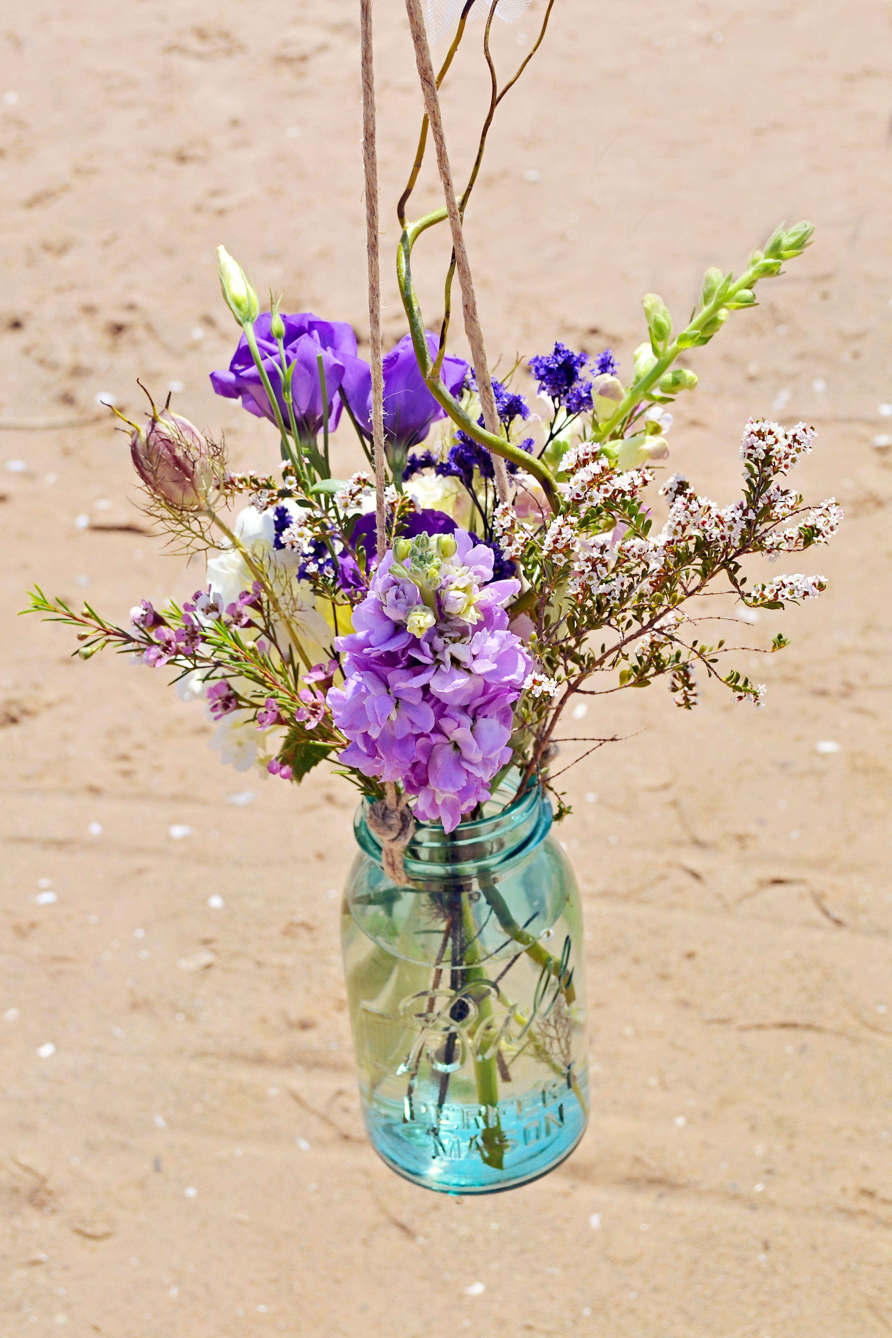 Purple flowers in glass mason jar vase Lake Huron beach wedding