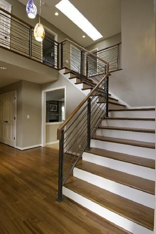 this builder grade stair was transformed by substituting a custom metal railing and cherry stair treads and railing cap to compliment the new Brazillian cherry floors that were installed.