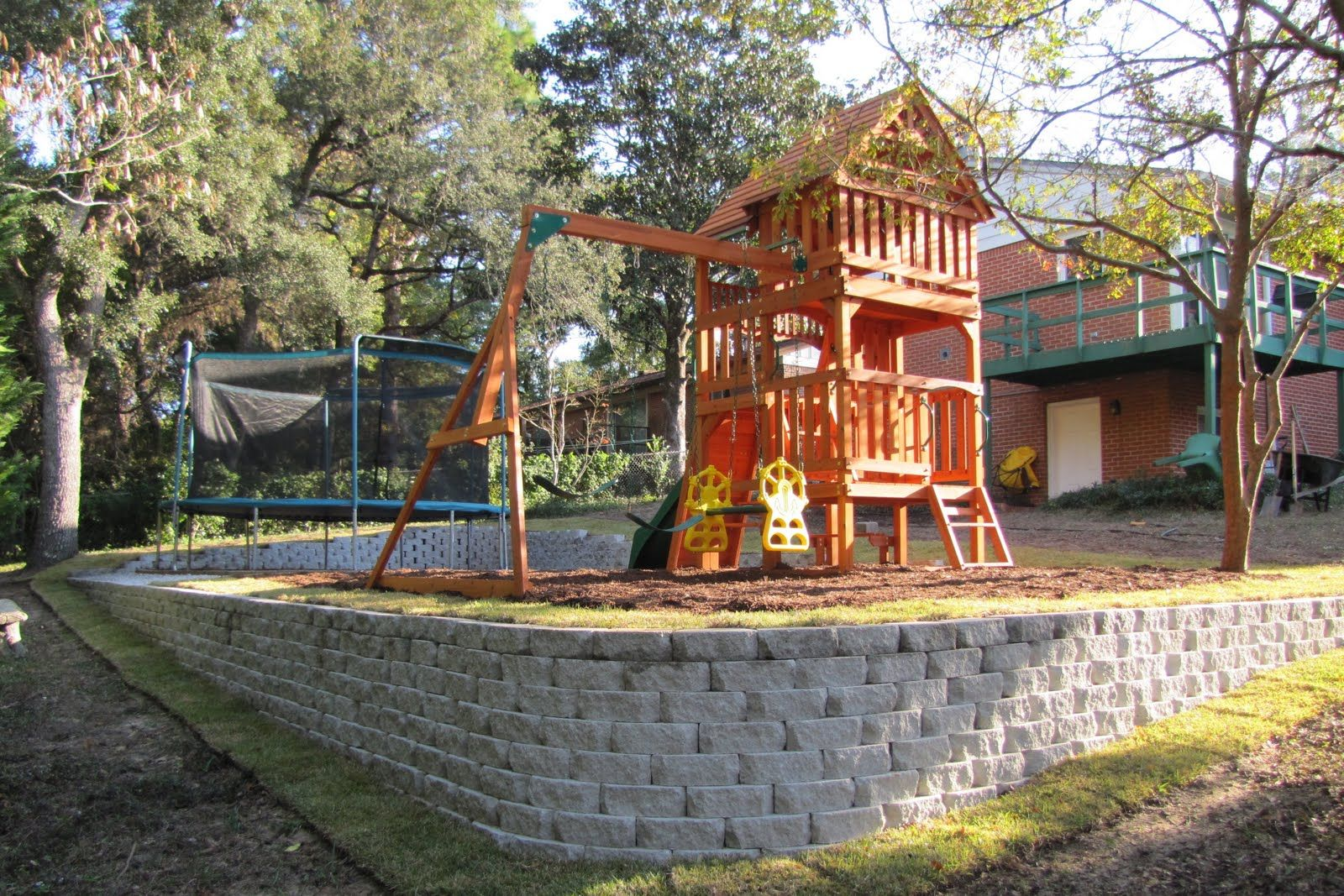Level play area and playscape. | Sloped backyard, Backyard ...