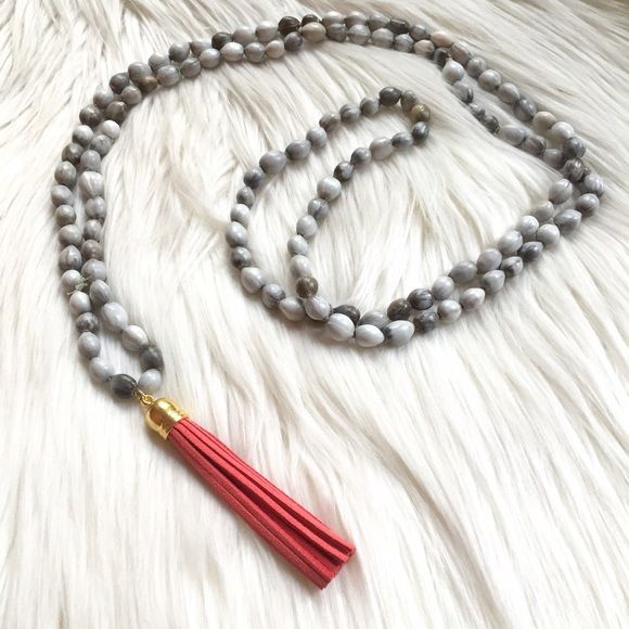 """Gray beaded necklace with coral leather tassel Beautiful handmade gray bean beaded necklace purchased in Peru with purple leather tassel. 25"""" in drop length on necklace with 3"""" leather tassel. Can be layered or double wrapped for your personalized look. beads are all unique shades, truly 50 shades of gray beads  Jewelry Necklaces"""