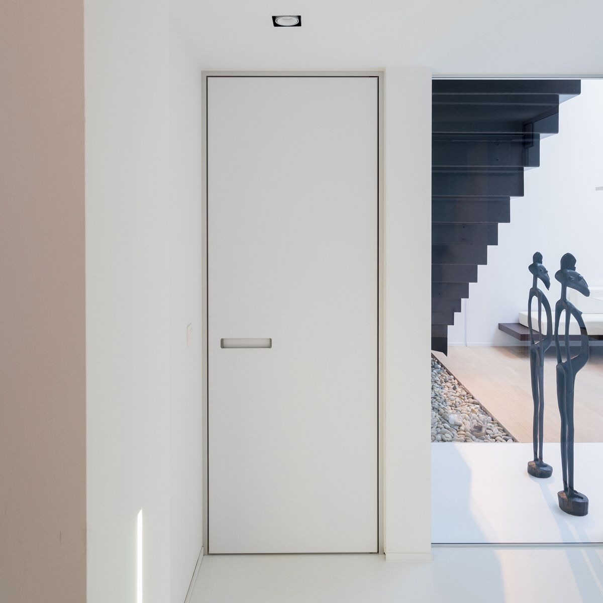 bdb887792a2 The minimalist aluminium Block-frame gives the door a frameless appearance.  Custom-made by Anyway Doors. Modern white interior ...