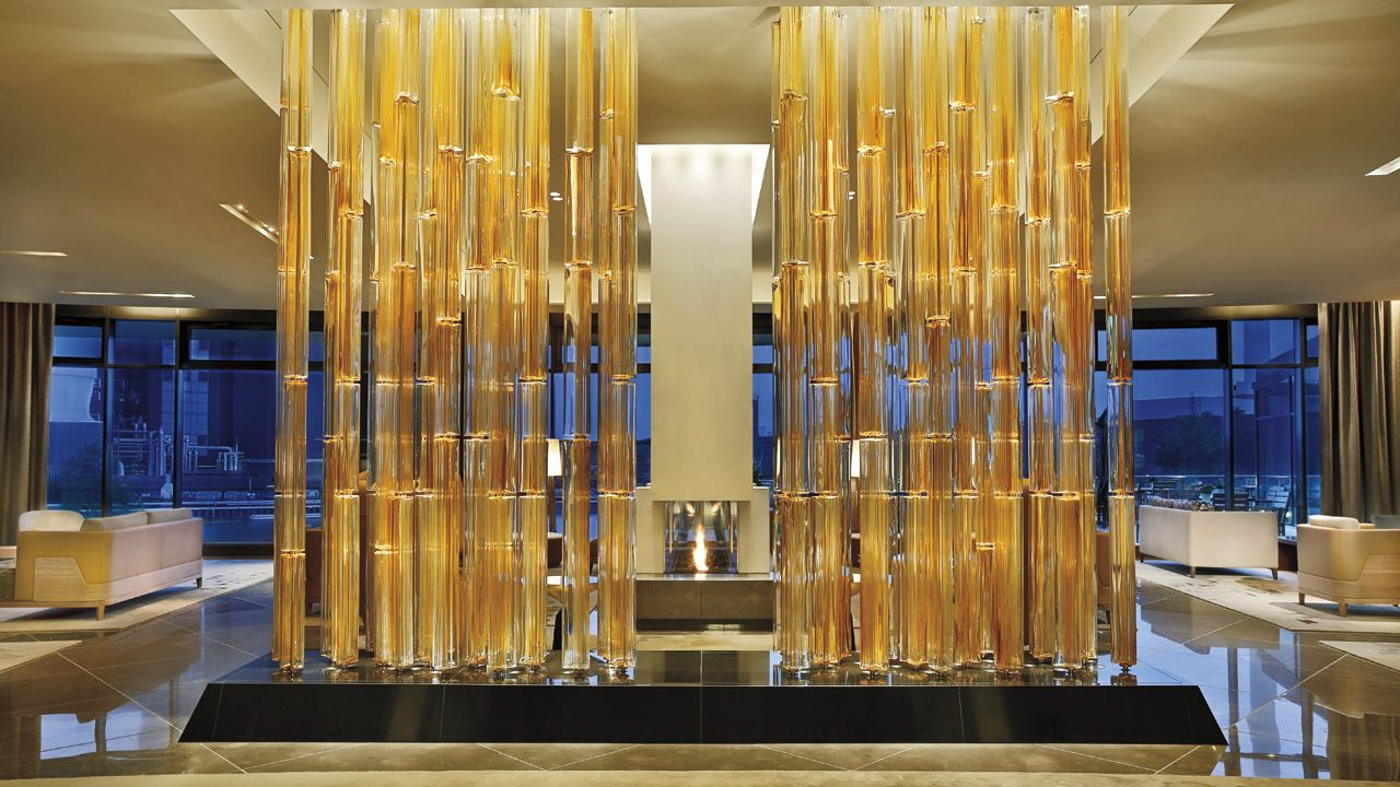 "The Ritz-Carlton, Wolfsburg Lobby Lounge, A ""glass forest"" sculpture surrounds guests who have tea in the Lobby Lounge."