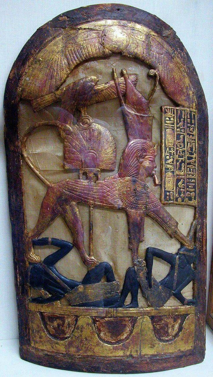 """ceremonial shield with King TutankhAmun represented as a sphinx (wearing the Nemes with the Uraeus and the Double Crown) trampling over two rebels (with black african features). On the top, Horus in His form of sacred falcon holding the 'shen'-ring, and the Winged Solar Orb. From the """"House of Eternity"""" of King TutankhAmun. Now in the Cairo Museum"""