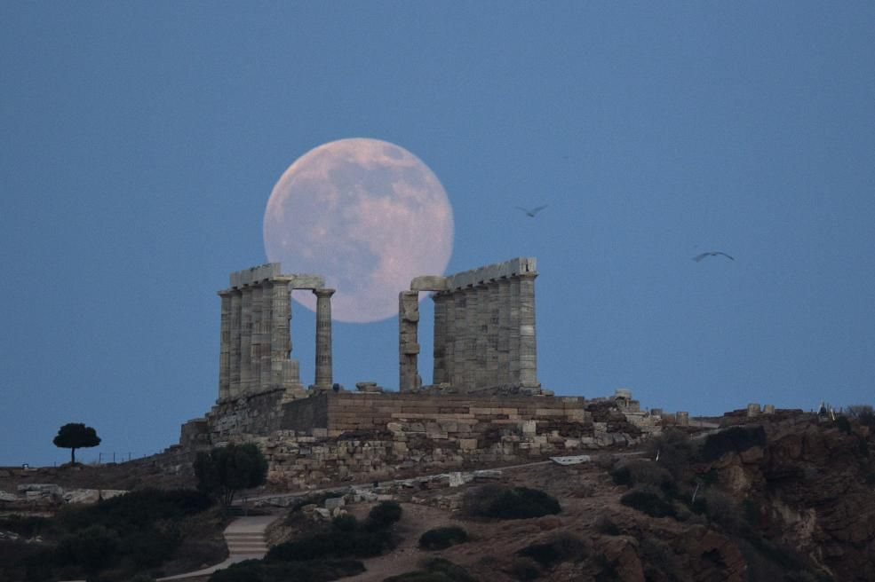 A full moon rises behind the ancient marble Temple of Poseidon at Cape Sounion, Athens, on the eve of the summer solstice.