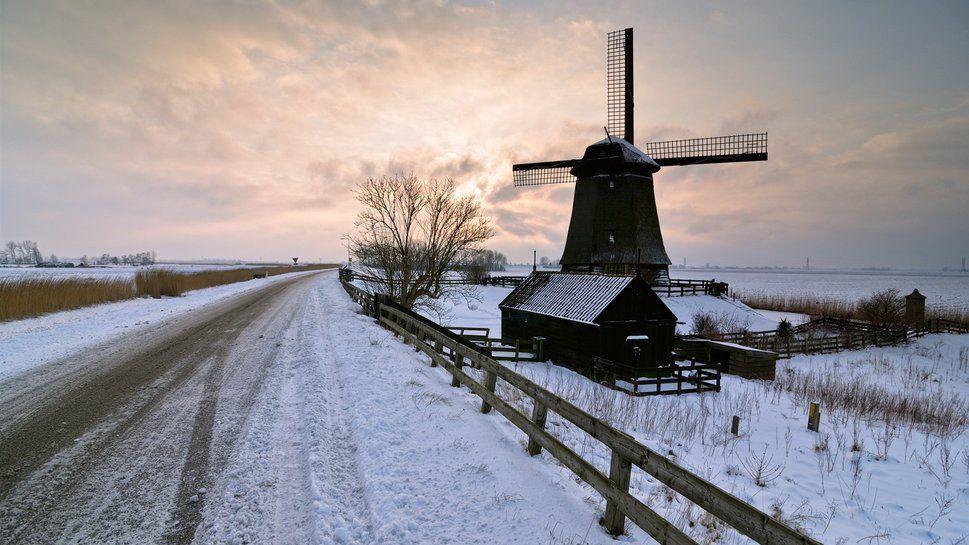 moinho de vento por uma estrada de país de inverno Vetor