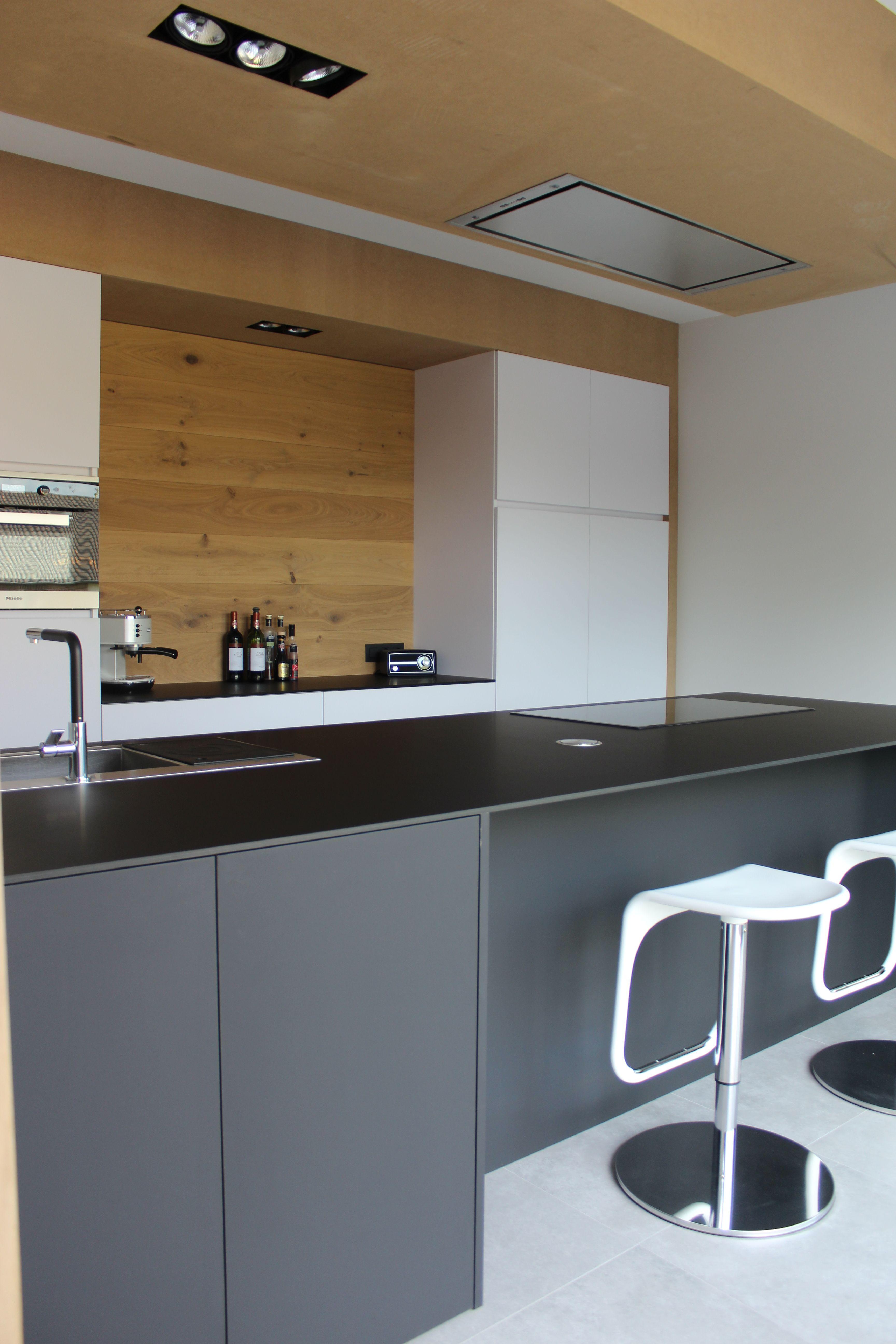 Moderne strakke keuken wit en zwart gecombineerd met hout kookeiland in materiaal fenix ntm for Deco moderne keuken