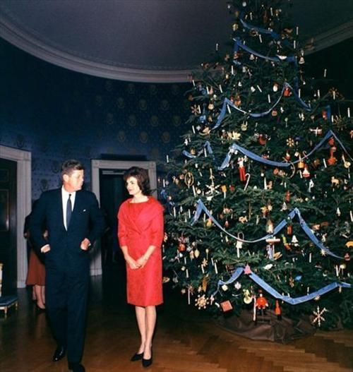 John F. Kennedy and Jackie Kennedy pose in front of the White House Christmas Tree, circa 1961.