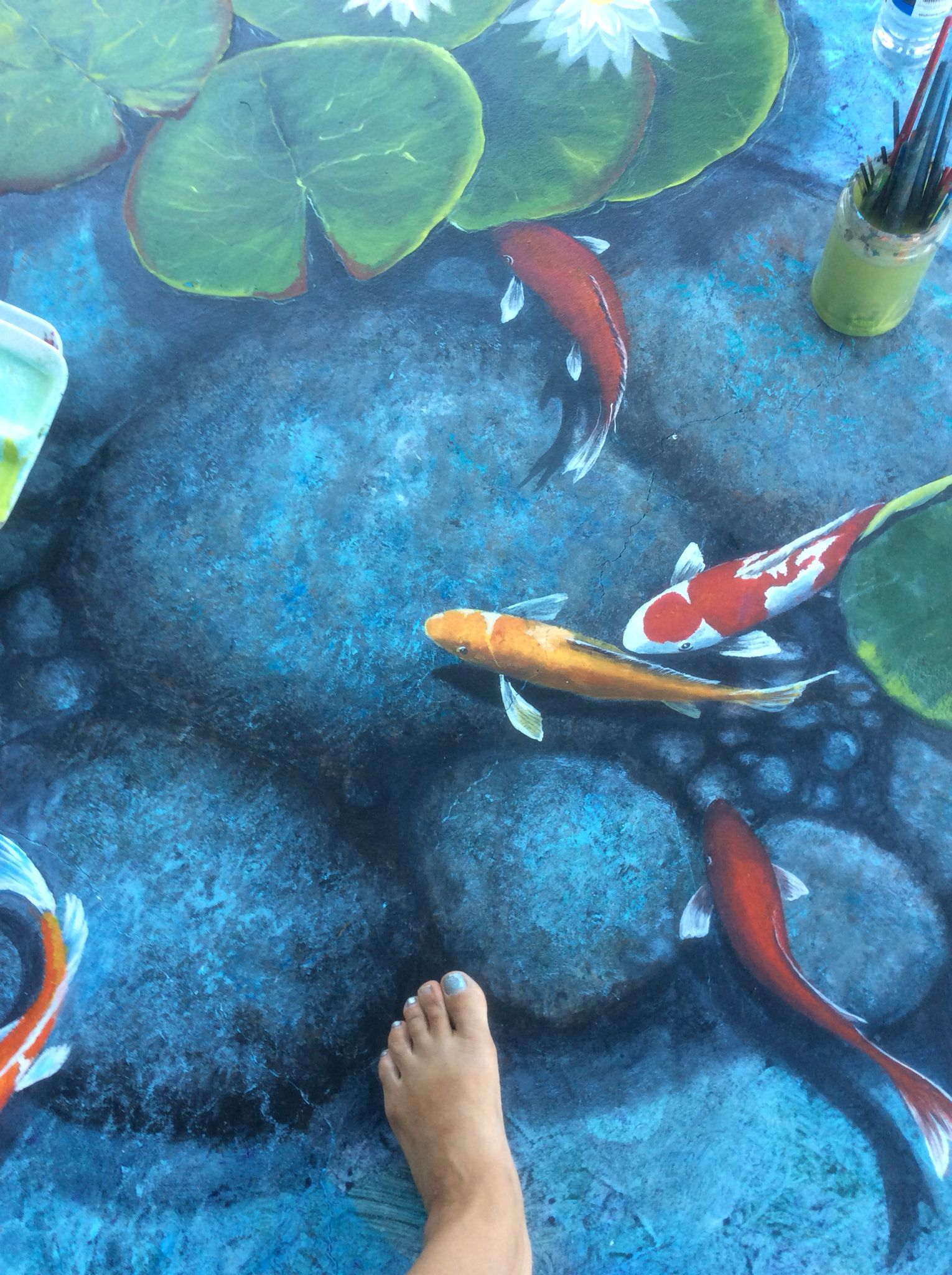 Trompe l'oeil koi fish pond on my lanai. Floor painting. Artwork and design by Louise Moorman.