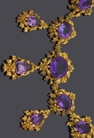 A mid 19th century gold and amethyst necklace and earring suite, circa 1840 The necklace composed of five graduating oval mixed-cut amethysts within a floral and scrolling ribbon surround, each suspending a detachable pear-shaped amethyst and gold drop of similar design, to a scalloped and beadwork back-chain