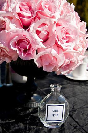 pink and black coco chanel inspired baby shower perfume bottles for centerpieces with roses and floral arrangement
