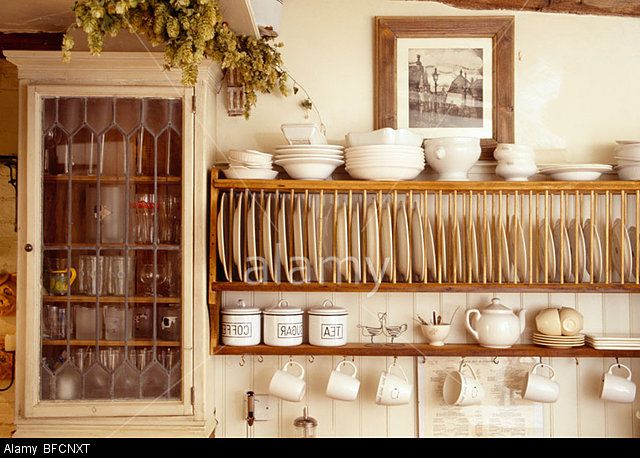 Stock Photo - Close-up of cream bowls on wooden plate rack beside small wall cupboard in cottage kitchen
