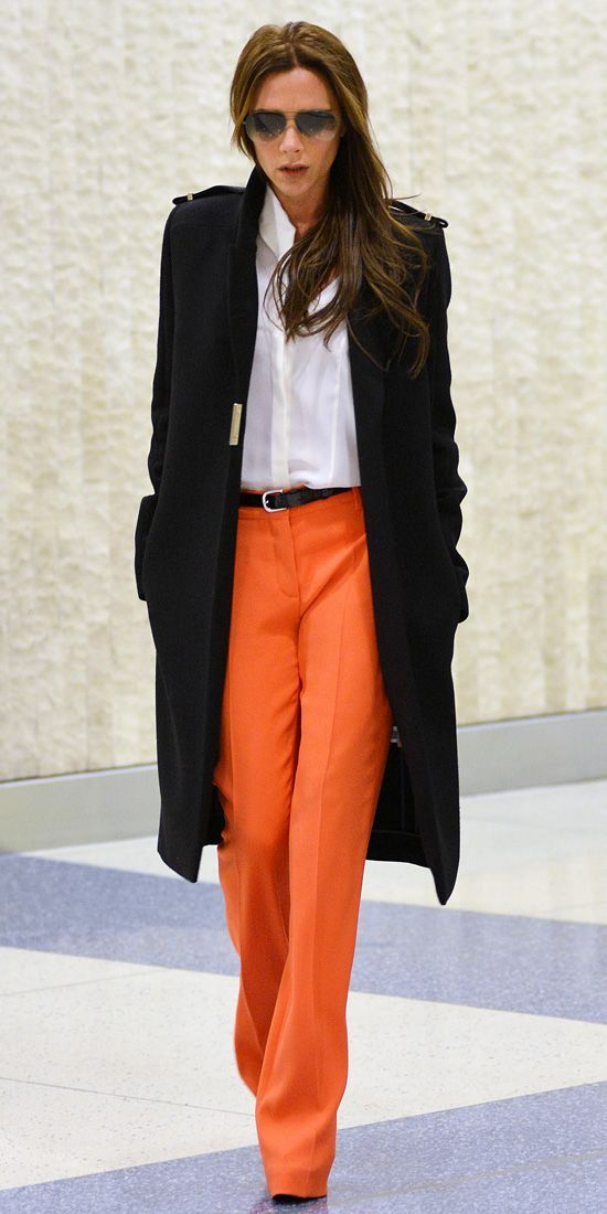 Victoria Beckham viste un abrigo negro, camisa blanca de negocios, pantalones anchos naranjas, cinturón de cuero negro  – Moda