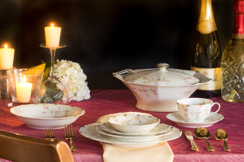 Candlelit setting of the fine china, with tureen in background.