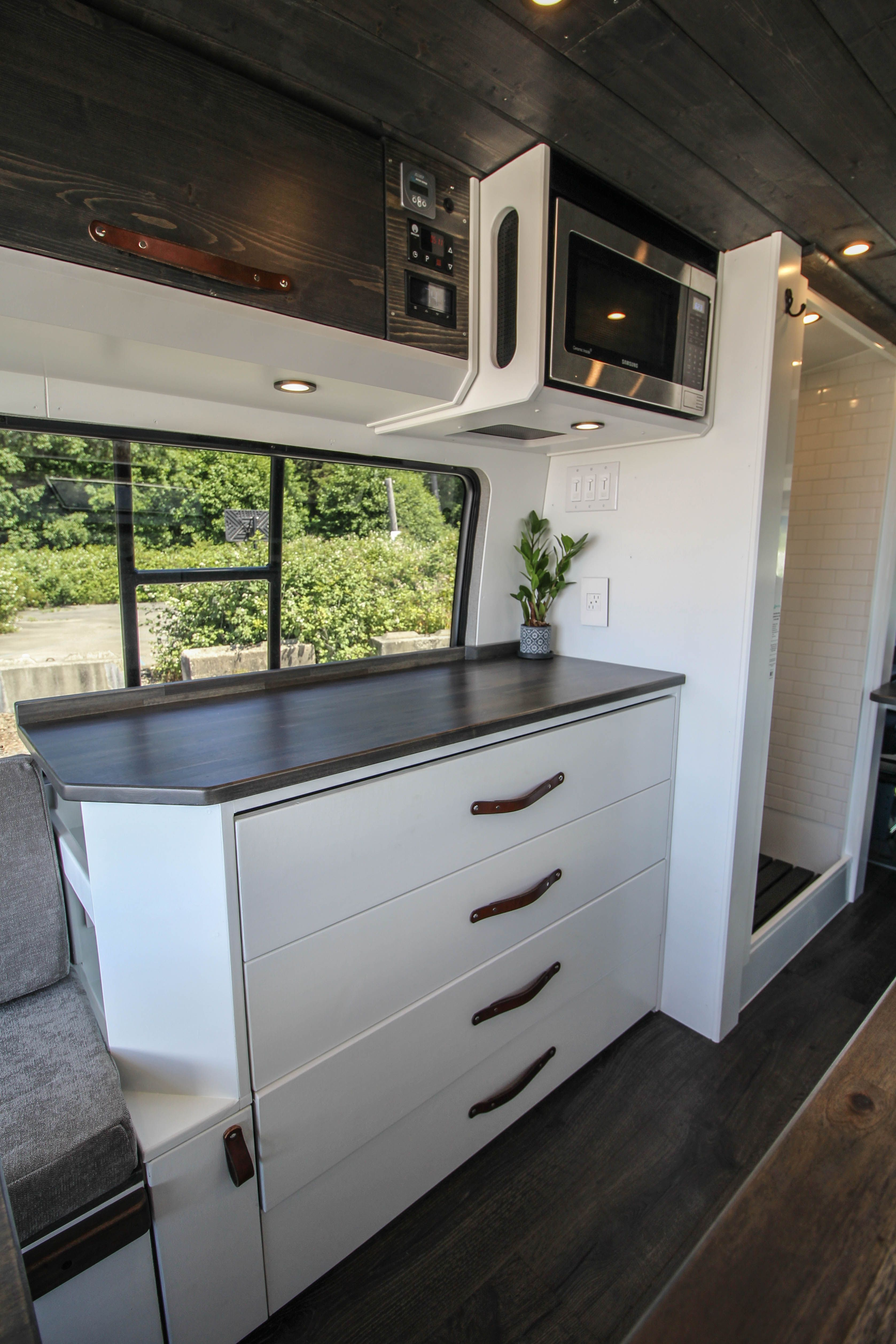Photo of Overhead cabinets, microwave, dresser/drawers and wet bath in Freedom Vans' Spri…