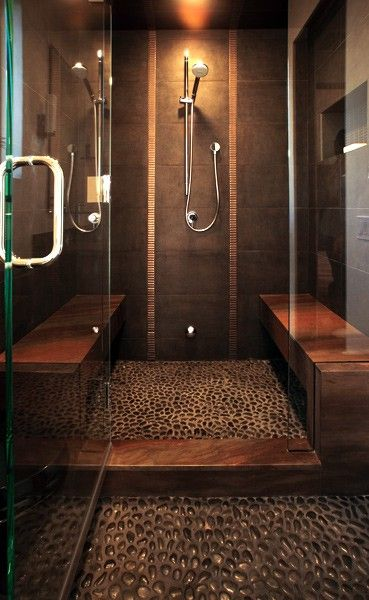tiled shower with stone pebble floor, glass doors and shower seats ...