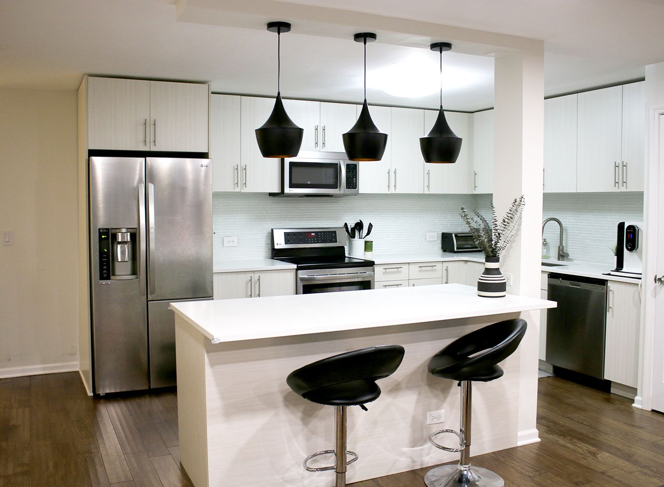 Modern kitchen with hardwood floors, black pendant