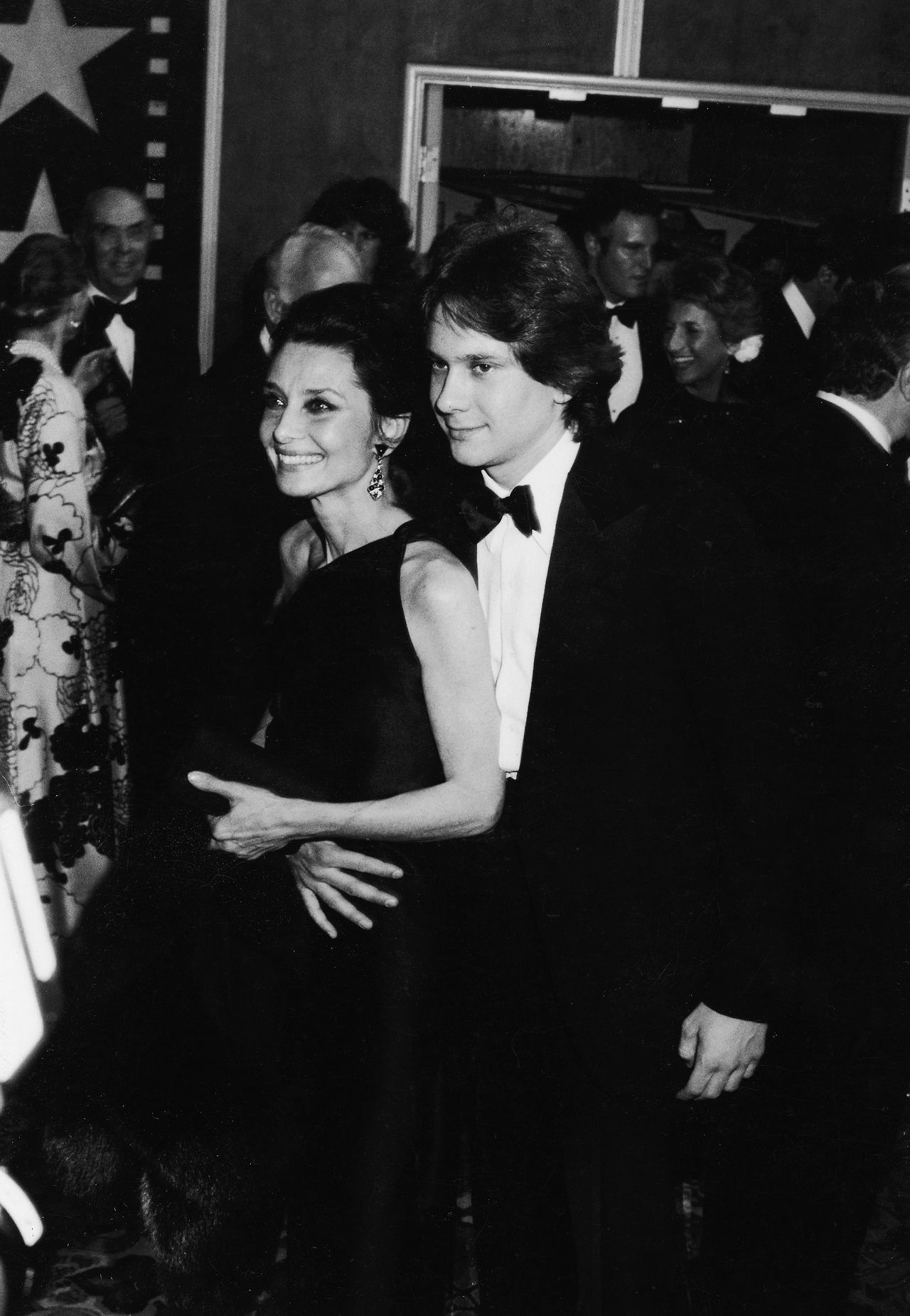 "Audrey Hepburn photographed with her son Sean Ferrer by Ron Galella during their arrival at ""American Film Institute Salute to Fred Astaire"" at the Beverly Hilton Hotel in Beverly Hills, California (USA), on April 10, 1981. -Audrey was wearing creations by Givenchy (one shoulder, evening gown made of black satin and clutch of his haute couture collection for the Spring of 1981), fur stole of Yves Saint Laurent and Bvlgari earrings."