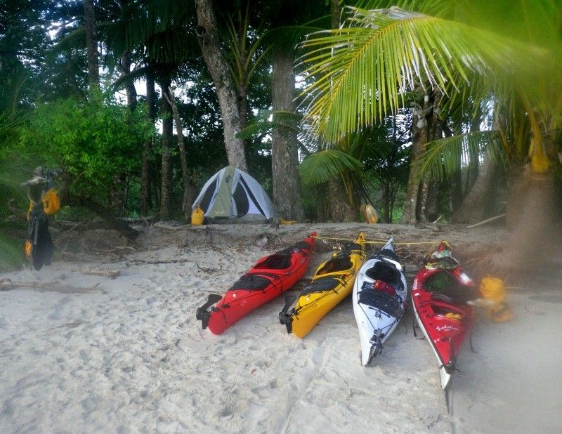 Photo of 4 kayaks beached on white sand in front of tent in the woods in Boca Chica area …