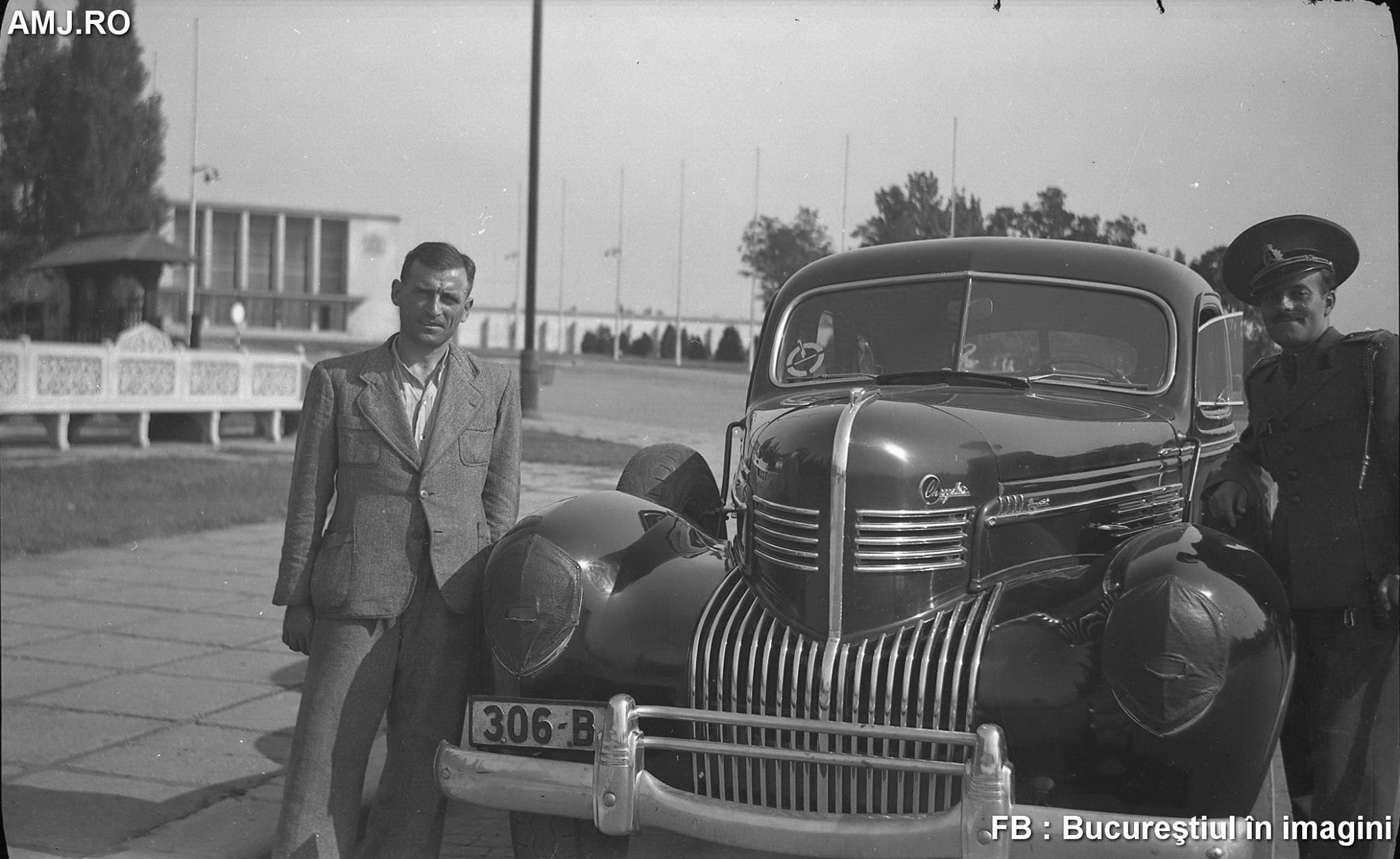 """București, 1943 sau 1944: automobil Chrysler, cu farurile camuflate, parcat în fața Gării Regale de la Băneasa (în piațeta unde se găsesc Vila Minovici, supranumită """"vila cu clopoței"""" și Fântâna Miorița). Pe fundal se observă gara și banca cu valoare artistică din fața Muzeului Minovici. În foișorul Vilei Minovici se găsesc clopoței care sună atunci când bate vântul, suficient de tare pentru a putea fi auziți din stradă…"""