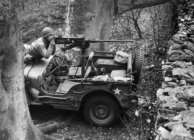 A soldier mans a  50 caliber machine gun mounted to a Willys MB