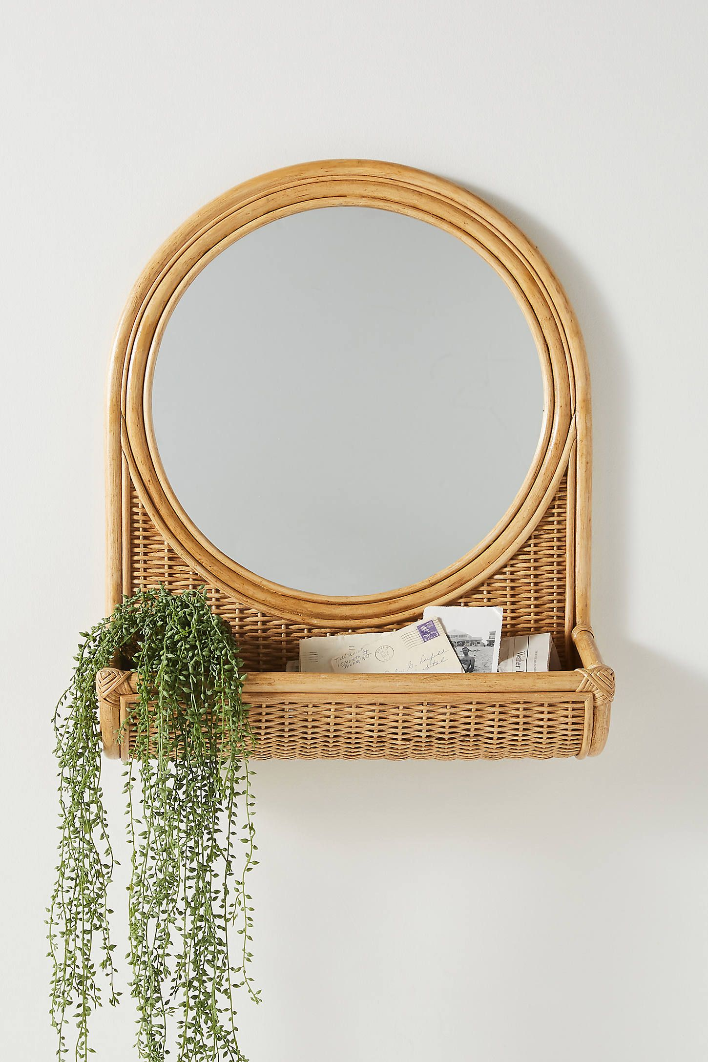 Hazel Round Rattan Mirror by Anthropologie in Beige, Wall Decor is part of Rattan mirror, Boho mirrors, Mirror decor, Bamboo mirror, Mirror wall decor, Unique mirrors - With a woven rattan frame and a convenient catchall basket attached, this mirror offers both function and texture to an entryway or a living space