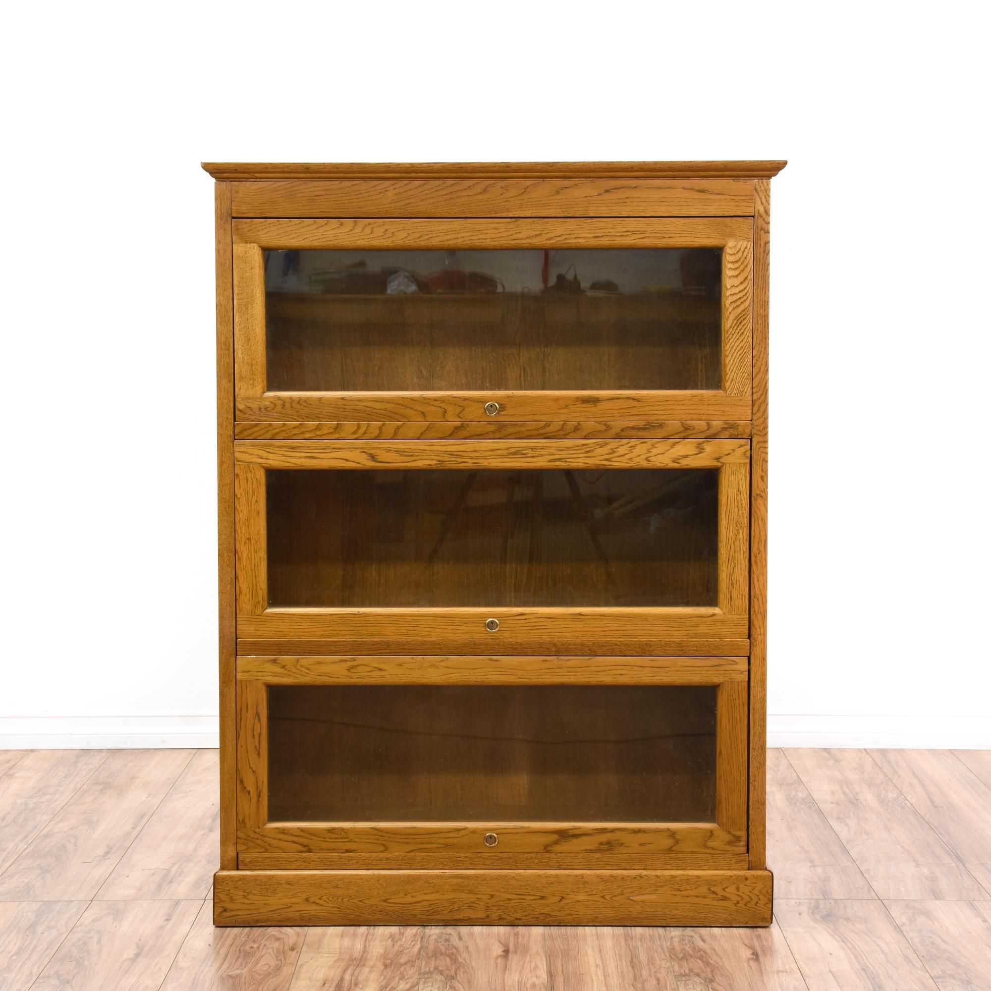This lawyer s bookcase is featured in a solid wood with a glossy oak