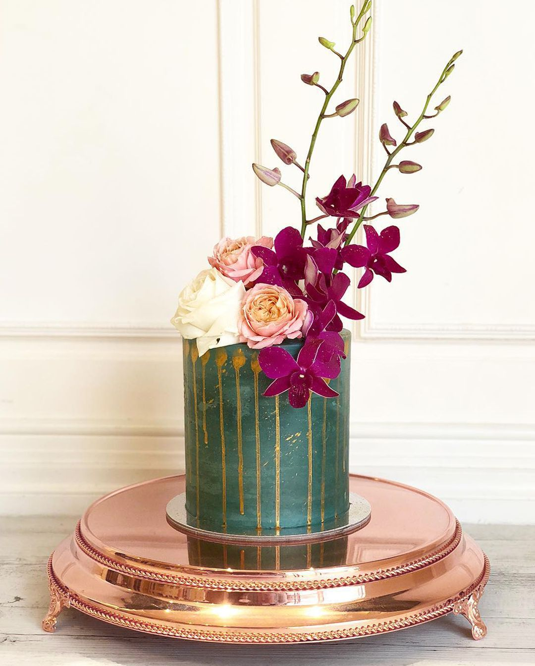 Beautiful small emerald cake with fresh orchids and roses