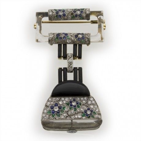 An Art Deco crystal, black enamel and gemset pendant watch, in the form of a handbag with crystal handle, all embellished with diamond, sapphire and emerald flowers, circa 1930.