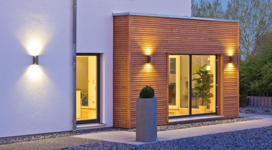 Eleganter Steingarten mit Beleuchtung vor Erker aus Holz