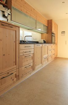 Modern geplante Holzküche mit Rahmenfronten und Griffen in