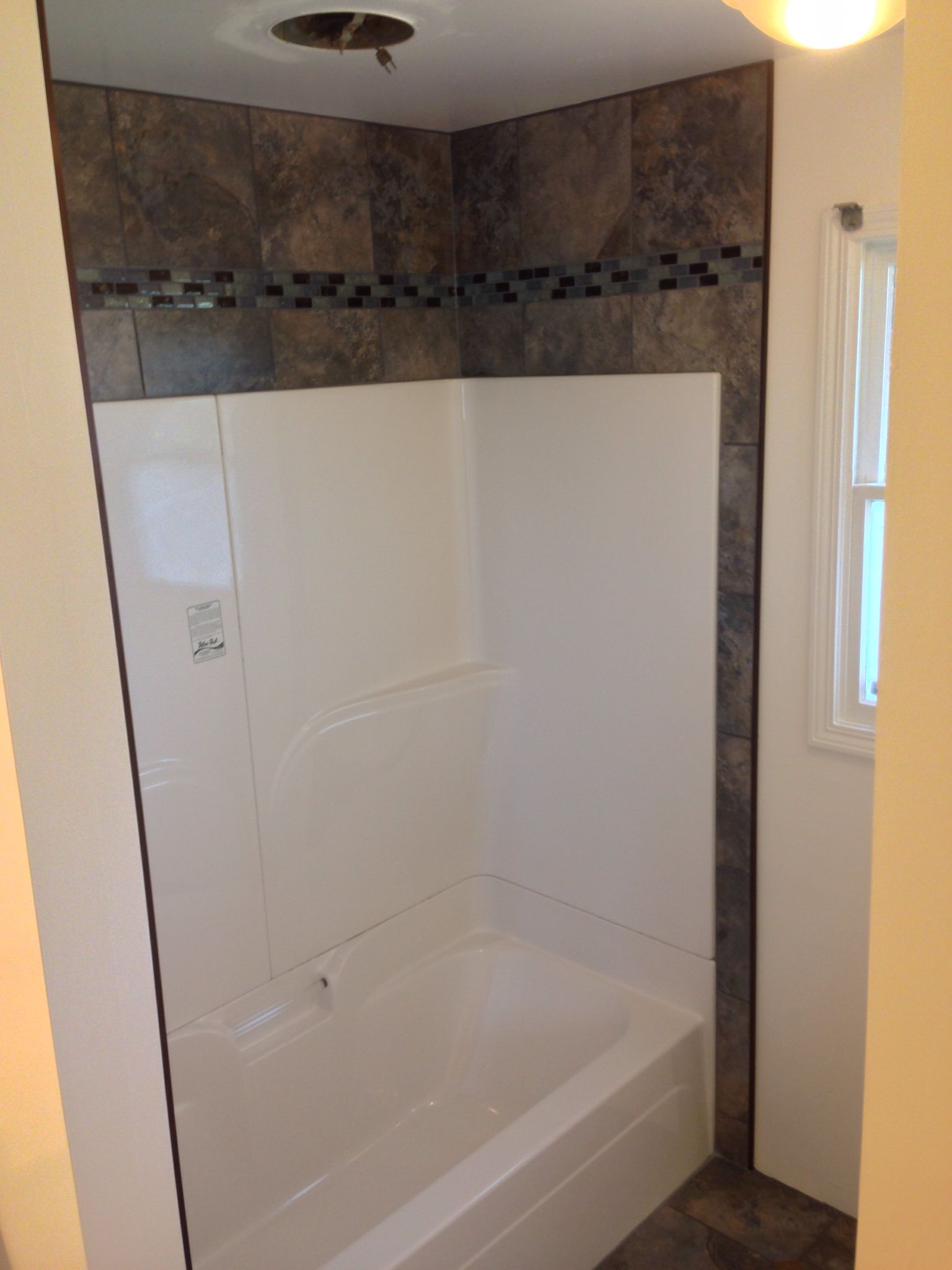 Want to dress up that empty space above your shower or tub Best way to tile around a bath