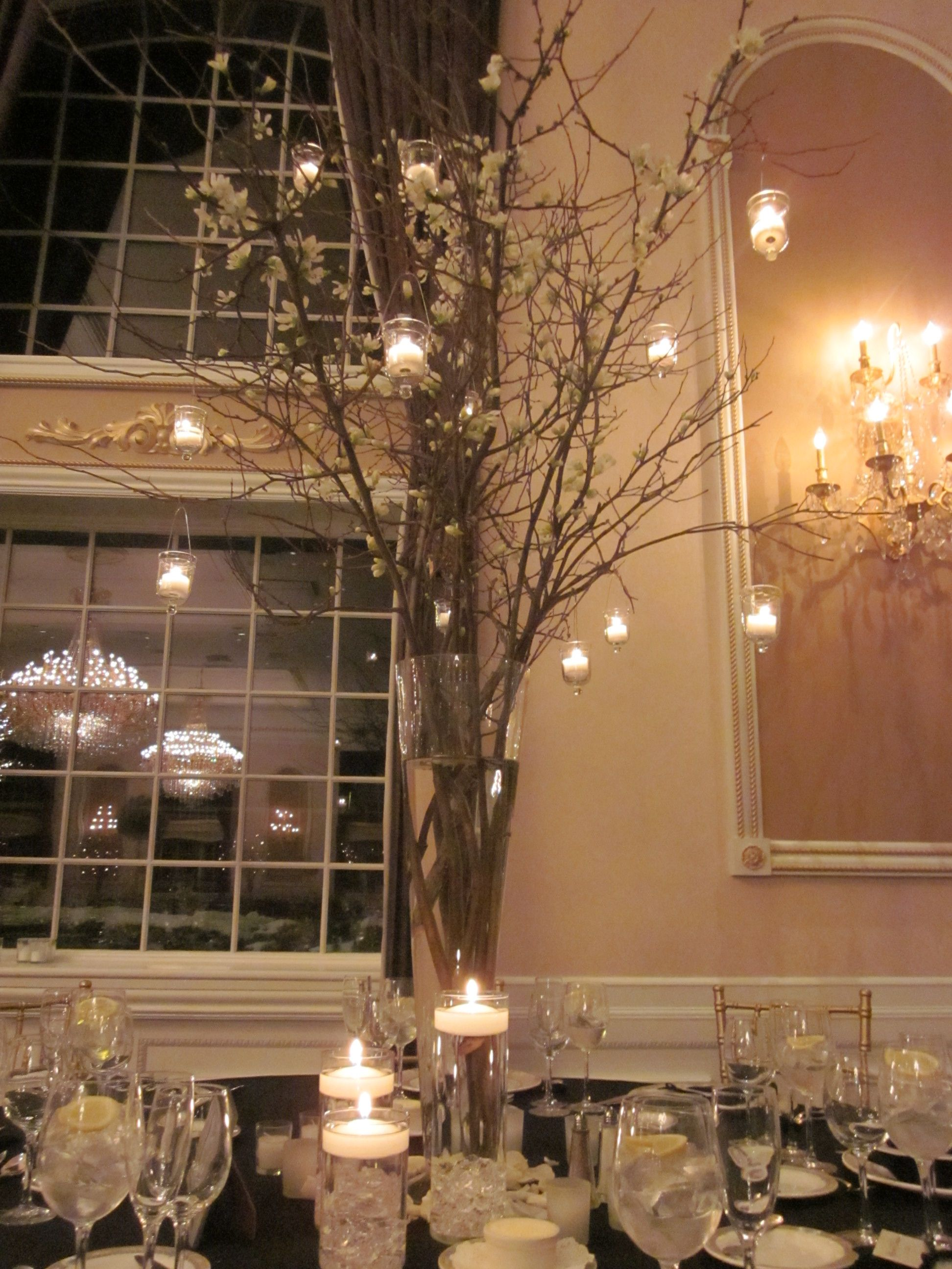 Tall centerpiece with white dogwood branches and hanging