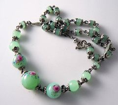 """Graduated green jade colored glass beads, covered with metallic silver tone caps. The 3 center beads are decorated with, molded in glass, pink flowers. Measures: 15 1/2"""" ( 39.5 cm ). Center bead: 1/2"""""""