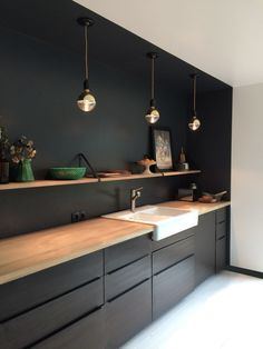 Black Kitchen Cabinets, Black Wall, Warmed By A Wooden Countertop And Wood  Shelves