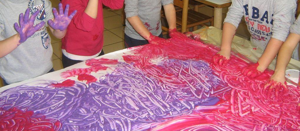 immagine di bimbi che dipingono usando le mani