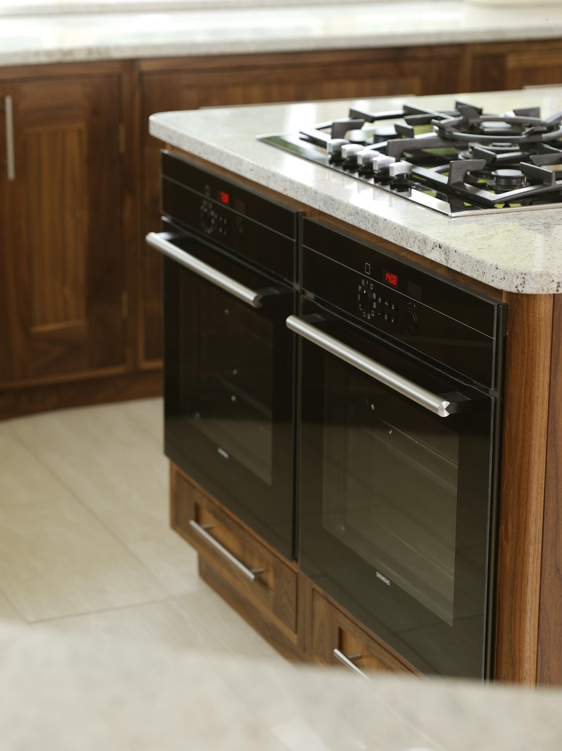 Walnut kitchen with kashmere white granite worktops solid walnut and walnut veneers