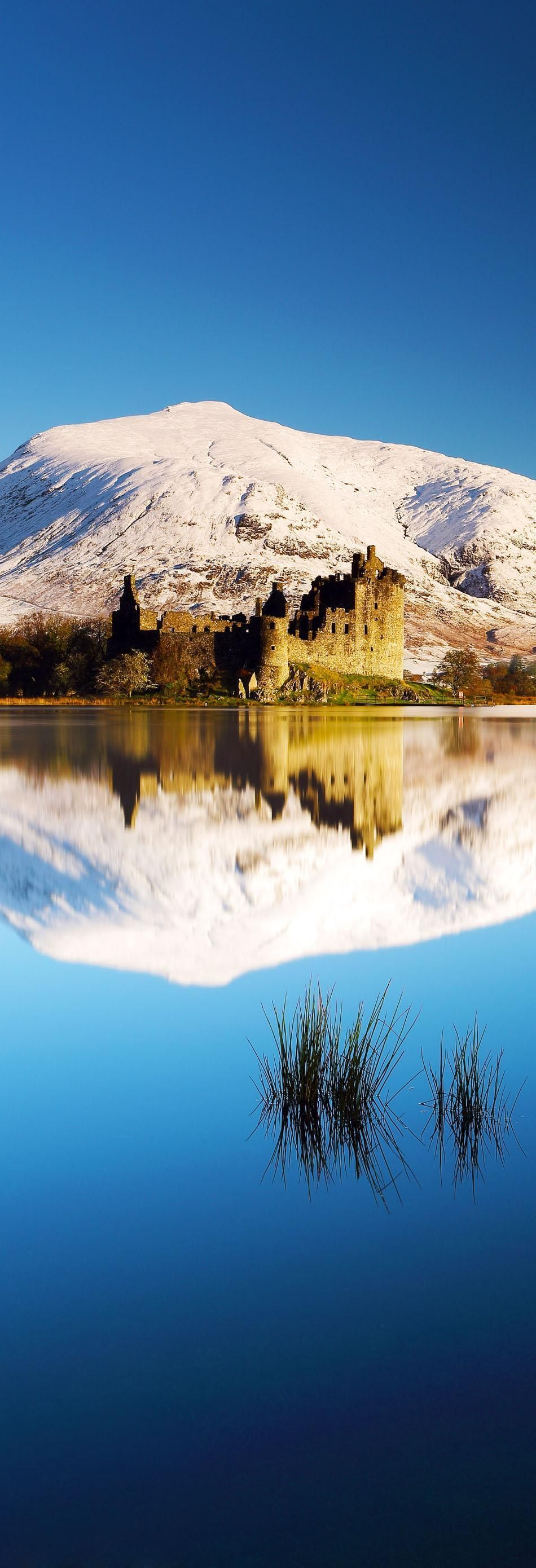 Kilchurn Castle and snow covered mountains reflecting off Loch Awe on a beautiful crisp morning. Dalmally, Scotland.