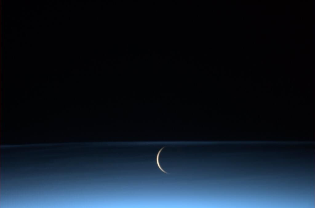 """canadian-space-agency:   A rare perspective! Luca Parmitano: """"The moon rises surrounded by noctilucent clouds."""" Photo Credit: Luca Parmitano"""