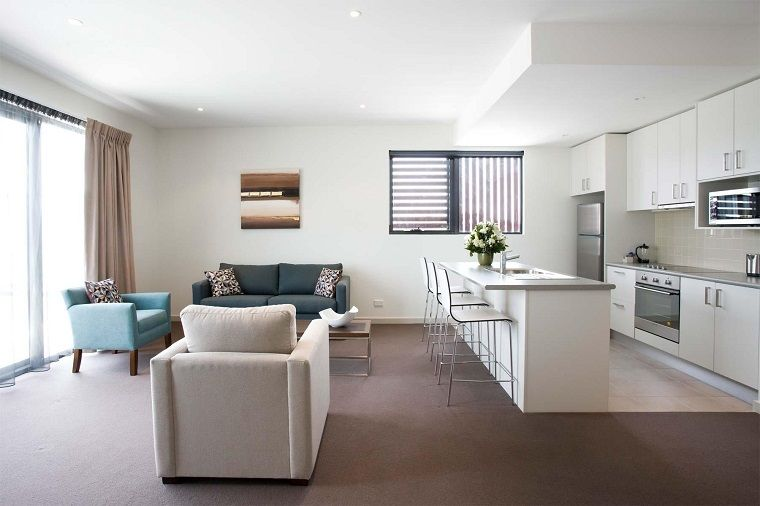 soggiorno con angolo cottura-mobili-bianchi-poltrone-azzurre ...